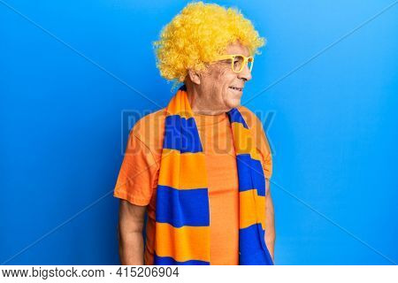 Senior hispanic man football hooligan cheering game looking to side, relax profile pose with natural face and confident smile.