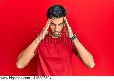 Young handsome man wearing casual tshirt over red background with hand on head, headache because stress. suffering migraine.