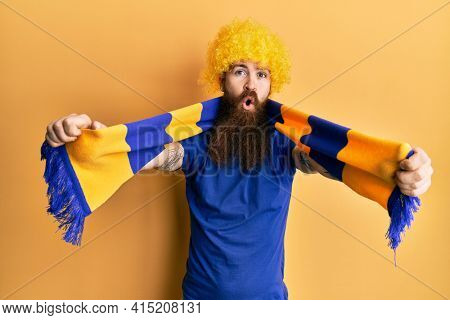 Redhead man with long beard football hooligan cheering game wearing funny wig afraid and shocked with surprise and amazed expression, fear and excited face.