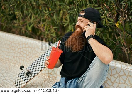 Young irish skater man talking on the smartphone and drinking soda at the park