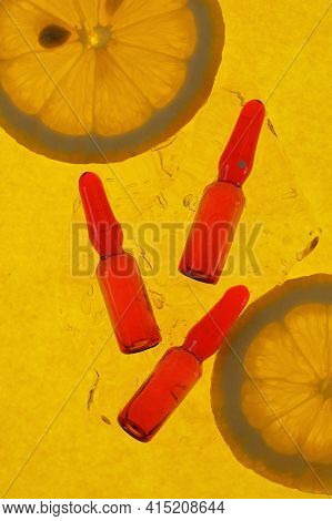 Vitamin C.serum With Vitamin C.red Ampoules Set And Lemons Slices In A Transparent Gel On A Bright Y