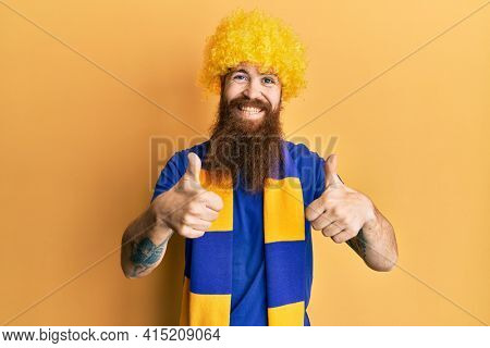 Redhead man with long beard football hooligan cheering game wearing funny wig approving doing positive gesture with hand, thumbs up smiling and happy for success. winner gesture.