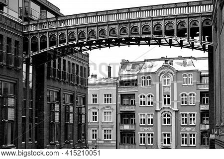 Metal Footbridge And Red Brick Wall In An Old Brewery In Poznan, Monochrome