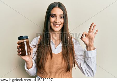 Beautiful brunette young woman holding soluble coffee doing ok sign with fingers, smiling friendly gesturing excellent symbol