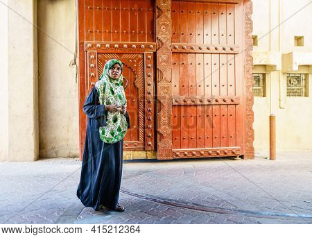 Nizwa, Oman, December 2, 2016: Middle-aged local woman is walking  through the town gates at Friday Market in Nizwa, Oman