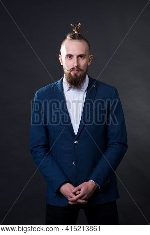 A Man With A Beard And A Fashionable Haircut In A Business Suit In The Studio On A Dark Background