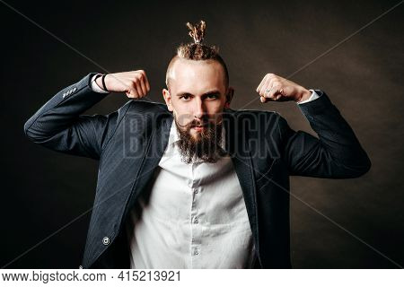 Portrait Of A Young Bearded Brutal Hipster Man Who Shows Muscle Strength In A Jacket And White Shirt
