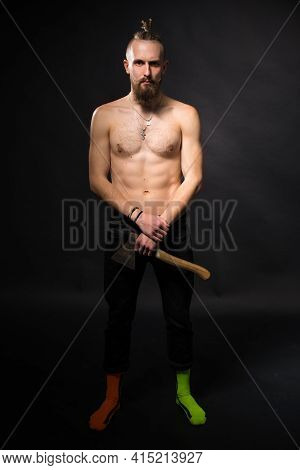A Young Man With A Thick Beard And A Long Mustache With An Ax Like A Viking On A Dark Background