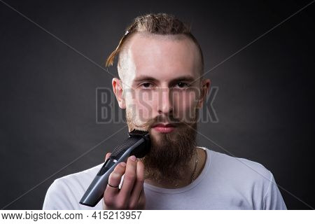 Young Handsome Bearded Man Shaves Thick Beard With Trimmer