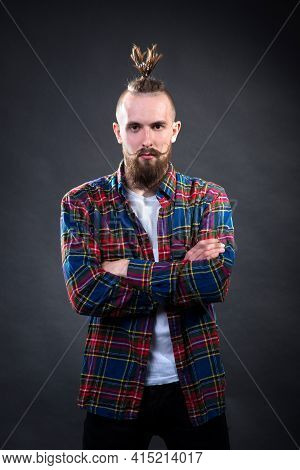 Young Serious Man With A Thick Beard And Mustache In A Checkered Shirt In The Studio On A Dark Backg