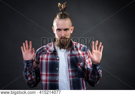 A Young Man With A Thick Beard And A Stylish Haircut Raised His Hands Up And Attracts Attention, Sto