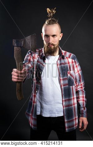 A Young Handsome Man With A Thick Beard And A Large Mustache In A Plaid Shirt Holds An Ax In His Han