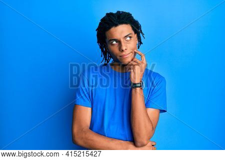 Young african american man wearing casual clothes thinking concentrated about doubt with finger on chin and looking up wondering