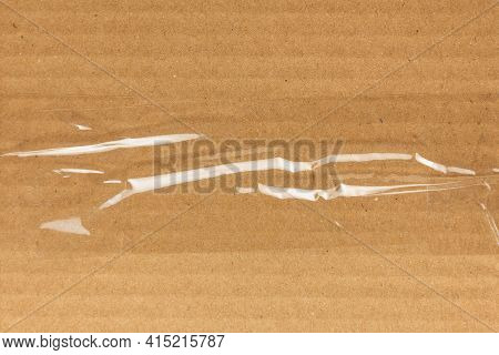 Sticky Transparent Tape On A Cardboard Box. Adhesive Tape  On The Cardboard Surface
