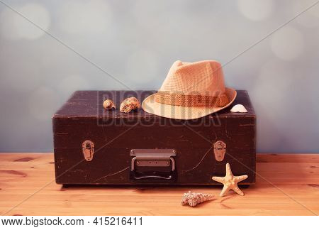 Vintage Wooden Suitcase, Hat, Starfish And  Seashells On Blue Background. Summer Holidays And Travel