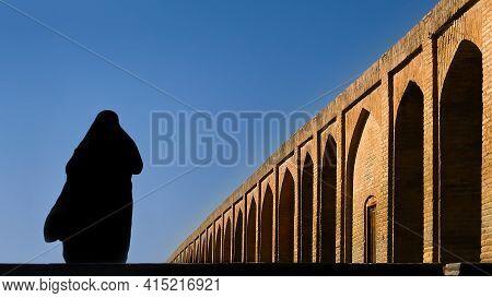 Silhouette Of A Persian Woman In National Dress On The Old Khaju (pol-e Khaju) Bridge In Isfahan. Ir