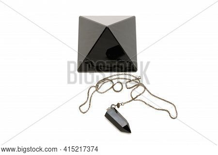Pyramid And Pendulum On Silver Chain Of Black Onyx. Isolated White Background.