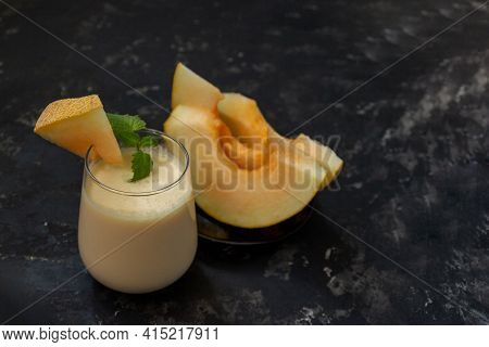 Milk Melon Smoothie On A Black Background. The Glass Is Decorated With A Slice Of Melon And Mint. In