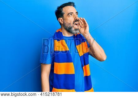 Middle age man with beard and grey hair football hooligan cheering game shouting and screaming loud to side with hand on mouth. communication concept.