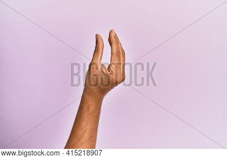 Arm and hand of caucasian young man over pink isolated background picking and taking invisible thing, holding object with fingers showing space