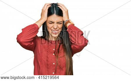 Young hispanic woman wearing casual clothes suffering from headache desperate and stressed because pain and migraine. hands on head.