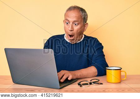 Senior handsome man with gray hair working at the office with laptop scared and amazed with open mouth for surprise, disbelief face