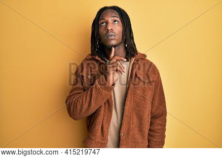 African american man with braids wearing brown retro jacket thinking concentrated about doubt with finger on chin and looking up wondering