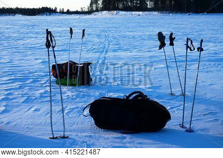 A Halt On The Ice, Group Of Skiers With Large Backpacks Crosses A Frozen Lake In The Transition To T