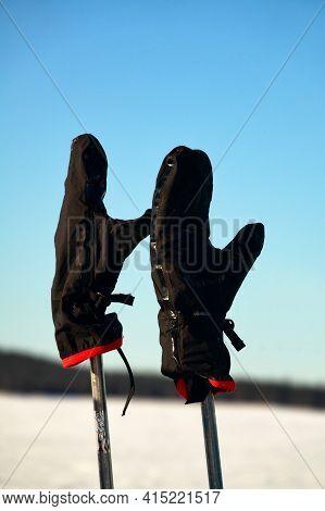 Attributes Of A Ski Trip. Ski Poles And Mittens On A Blue Sky Background. Halt