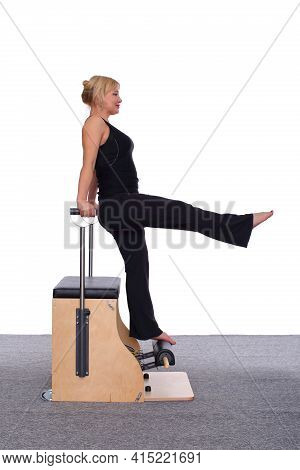 A 50-year-old Trainer Is Practicing Pilates On A Machine. She Stands On Her Toes And Holds Herself W