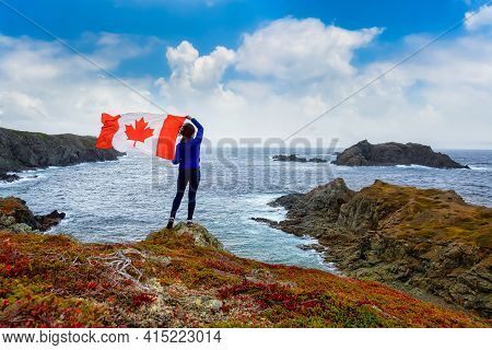 Adventurous Woman Holding A Canadian Flag On A Rocky Atlantic Ocean Coast During A Cloudy And Blue S