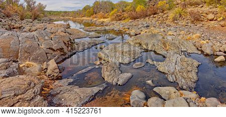 Reflecting Pools Of Water In Devil Dog Canyon Near Drake Arizona. The Boulders In The Water Are Volc