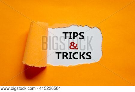 Tips And Tricks Symbol. Words 'tips And Tricks' Appearing Behind Torn Orange Paper. Beautiful Orange