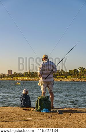 Father and son fishing at coast of river plate river, montevideo, uruguay