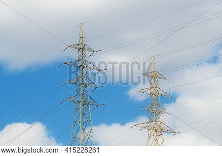 View On Two High Voltage Electric Transmission Towers Against A Cloudy Sky In Switzerland