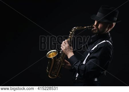 Handsome Man In Stylish Clothes And Hat Standing Over Black Background With Saxophone In Hands. Conc