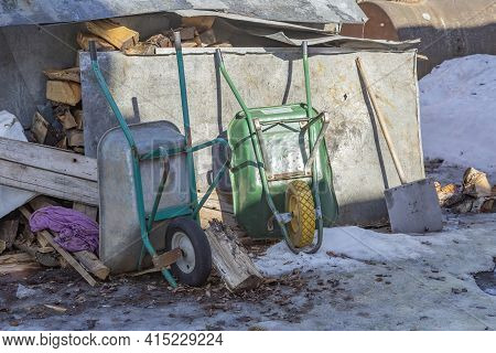 Two Old Hand Household Wheel Barrows In The Backyard
