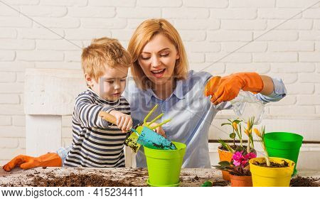 Springtime. Mother With Little Son Planting Flower. Family Relationships. Care For Plants. Gardening