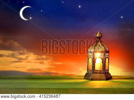 Islamic greeting  Eid Mubarak card for Muslim Holidays.Eid-Ul-Adha festival celebration.Ramadan Kareem background. Lantern lightning on wooden table.