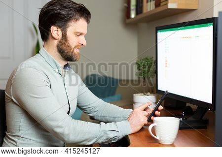 Man Taking Video Call On His Cell Phone Working From Home On Desktop Computer.