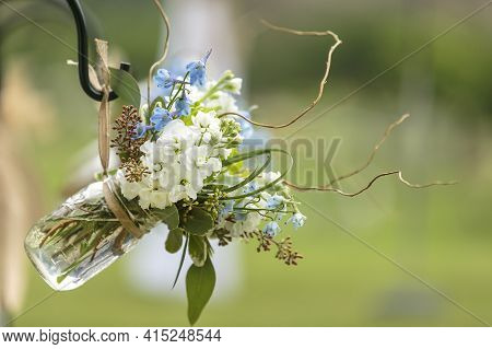 Blue And White Flowers In Mason Jars As Decor For Seating End Rows At A Wedding Ceremony
