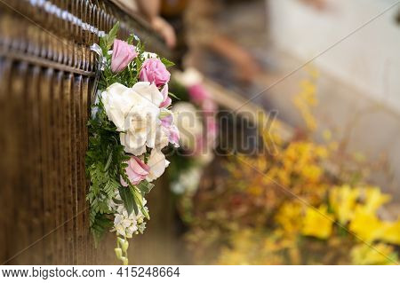 Pink And White Bouquet Of Roses Hanging From A Church Railing For A Wedding Ceremony
