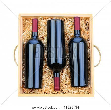 Closeup of three red wine bottles in a wooden case with packing straw. Overhead shot on a white background.