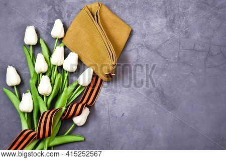 May 9. St. George Ribbon, Military Cap With White Tulips On A Gray Background. The Traditional Symbo