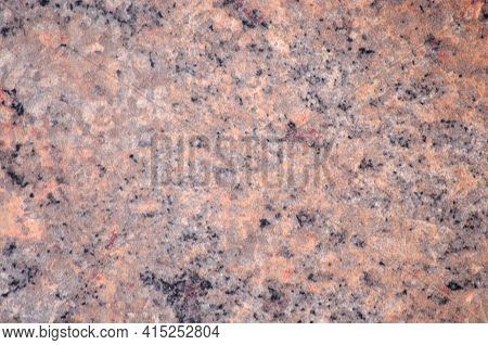 Natural Brown Granite, A Flat Surface Of Polished Stone With Small Black Blotches.