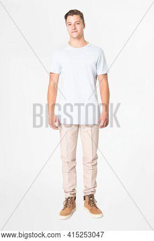 Man in white t-shirt and beige slacks full body