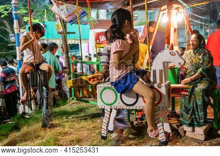 Howrah, West Bengal, India -14th April 2019: Girl Child Riding On Nagordola- A Traditional Amusement