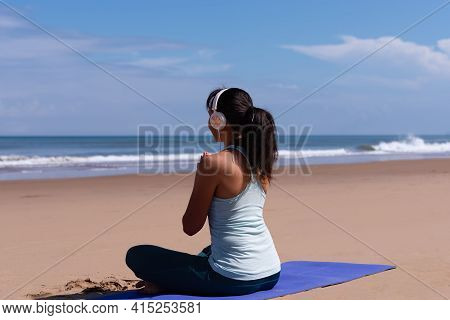 People, Fitness, Music And Healthy Lifestyle Concept - Asian Girl Meditating Listening The Music Wit