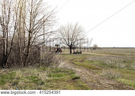 An Old Tractor In A Village In The Distance. Ruins And Old Equipment In The Village. Trail To The Tr