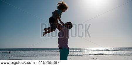 Father Throws Son Up Against The Blue Sky. Handsome Man Father Carrying Young Boy Son. Happy Dad Hol